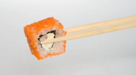 hashi: Sushi with red caviar in bamboo chopsticks. Stock Photo