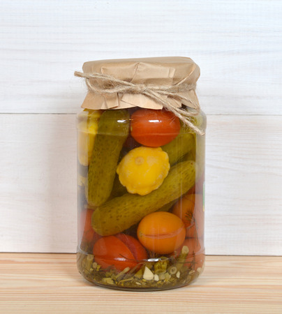 Glass Jar Of Preserved Vegetables on a wooden table and white wall. Imagens
