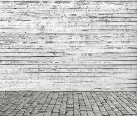 Old white wooden wall and cobblestone floor.