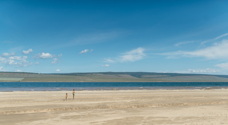 cool off: boy and girl running into the sea soon to take a dip and cool off . Stock Photo