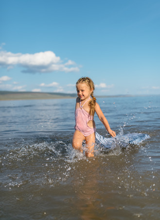 beach clothes: little girl running through the water with a splash . in her hands cloth.