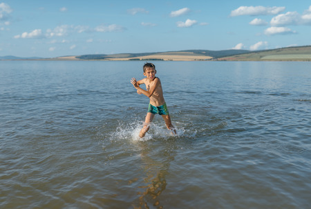 very cold: unhappy boy runs out of very cold water