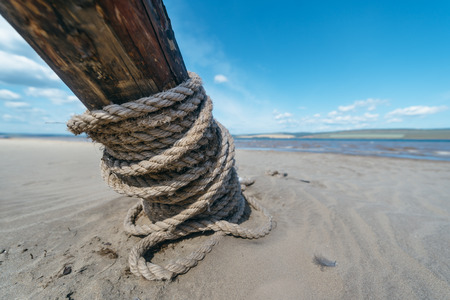 pierce: keep the sea. Pierce tied to special dug in the sand log. Stock Photo