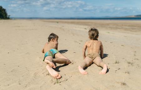 sandalia: niño y niña se arrastra en la arena dejando huellas. Jugando en la arena. Mira en la distancia.