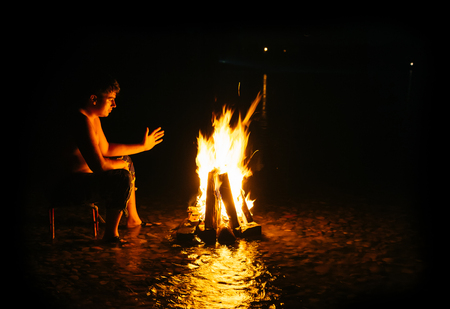 People - Bonfire on the river bank . Sparks, flames and other wonderful backgrounds for your text. photo framed wholly in black. 스톡 콘텐츠
