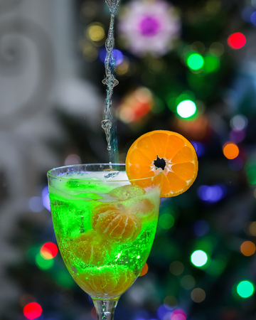 intoxicating: Pours champagne in a glass with ice and tangerines .