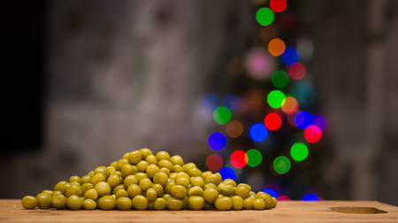 intoxicating: Peas on a cutting board. In the background - Christmas tree. The process of preparing the salad. Stock Photo