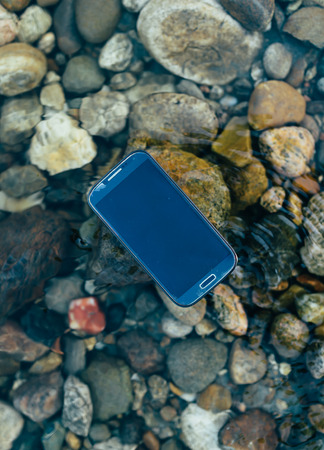 supported: Lost man modern smartphone supported floating on the water. Stock Photo