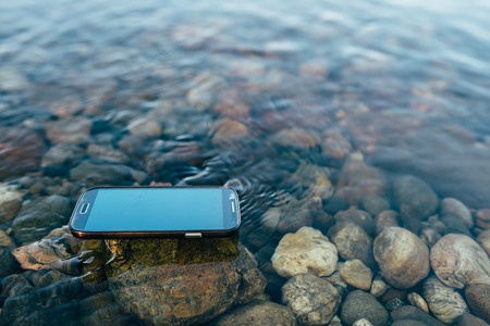 durable: Lost man modern smartphone supported floating on the water. Stock Photo