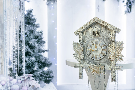 10 12 years: Old cuckoo clock on the background of the Christmas tree showing the time remaining until Christmas. Time 23.45 11.45 Stock Photo
