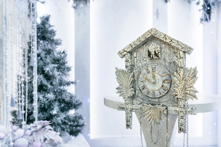 10 12 years: Old cuckoo clock on the background of the Christmas tree showing the time remaining until Christmas. Time 23.50 11.50