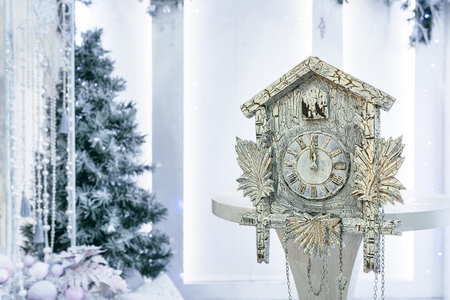 10 12 years: Old cuckoo clock on the background of the Christmas tree showing the time remaining until Christmas. Time 00.00 12.00 Stock Photo