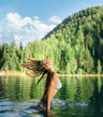 bathed: Forest Fairy. The girl bathed in a warm lake. Beautiful splashes of water from the hair.