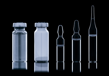 constricted: Different types of vials of different liquids. Isolated on a black background. Stock Photo