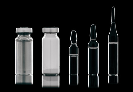 Different types of vials of different liquids. Isolated on a black background. Stock Photo