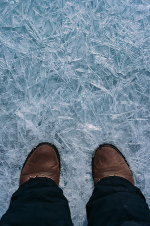 thin ice: Legs traveler in shoes standing on thin ice and a beautiful ice.