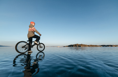 traumatic: Girl standing on a bmx on the beautiful and dangerous ice.