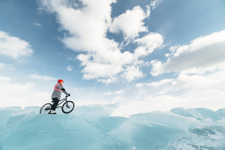 traumatic: Girl standing on a bmx on the beautiful and dangerous ice. Ice the deepest lake in the world. This is Lake Baikal.