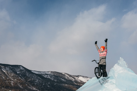 successful campaign: Girl standing on a bmx on the beautiful and dangerous ice and enjoys a successful campaign. Ice the deepest lake in the world. This is Lake Baikal.