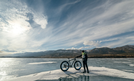 they are watching: Fatbike (also called fat bike or fat-tire bike) - Cycling on large wheels. Cyclist holding a bike and watching the sunset. They are standing on the frozen lake.