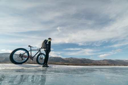 they are watching: Fatbike (also called fat bike or fat-tire bike) - Cycling on large wheels. Cyclist holding a bike, and watching the sunset. They are standing on the frozen lake.