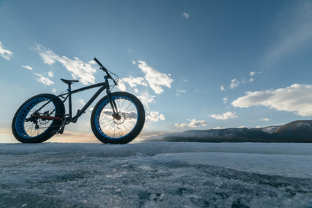 stands: Fatbike (also called fat bike or fat-tire bike) - Cycling on large wheels. Bike stands on the background of sunset on ice.