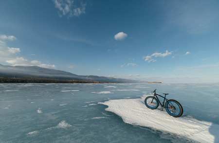 snow tire: Fatbike (also called fat bike or fat-tire bike) - Cycling on large wheels. Bicycling is at sunset on the ice. Stock Photo