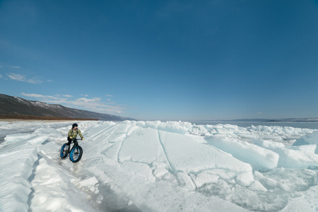Fatbike (also called fat bike or fat-tire bike) - Cycling on large wheels. Extreme girl sitting on the bike on snow melted ice. The Lake Baikal.