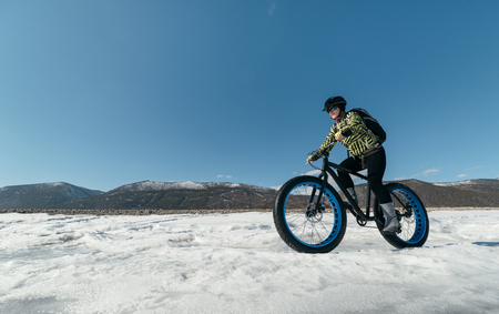 Fatbike (ook wel vet fiets of vet-band fiets) - Fietsen op grote wielen. Extreme meisje rijdt op een fiets op sneeuw gesmolten ijs. Het Baikalmeer. Stockfoto