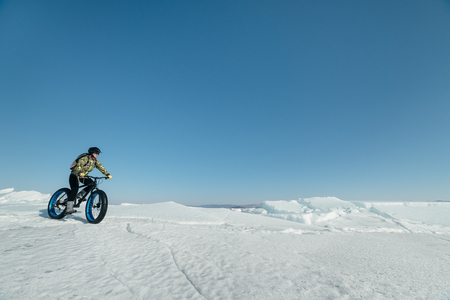 spinning: Fatbike (also called fat bike or fat-tire bike) - Cycling on large wheels. Extreme girl riding a bike on snow melted ice. The Lake Baikal. Stock Photo