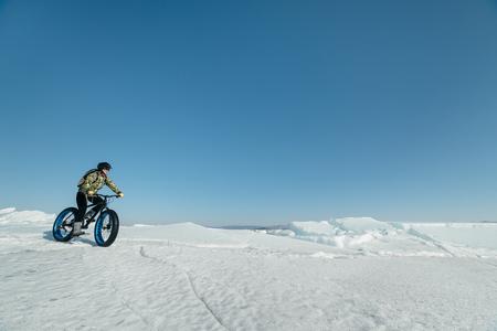 Fatbike (ook wel vet fiets of vet-band fiets) - Fietsen op grote wielen. Extreme meisje rijdt op een fiets op sneeuw gesmolten ijs. Het Baikalmeer.
