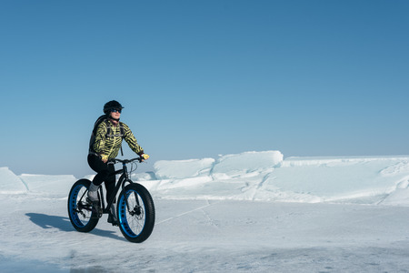 Fatbike (also called fat bike or fat-tire bike) - Cycling on large wheels. Extreme girl riding a bike on snow melted ice. The Lake Baikal. Stock Photo