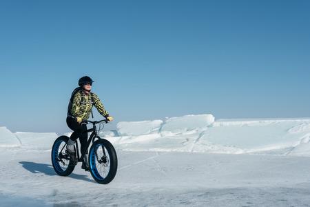 gravedad: Fatbike (también llamada moto o en bicicleta de grasa grasa neumático) - Ciclo en las ruedas grandes. Muchacha extrema andar en bicicleta en la nieve se derritió el hielo. El lago Baikal.