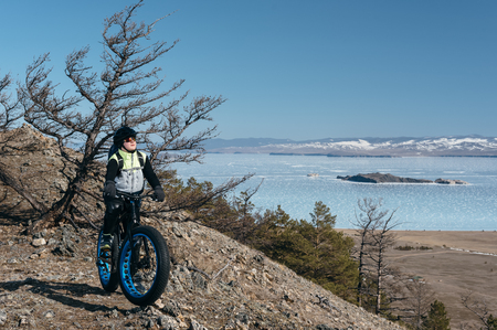 Fatbike (also called fat bike or fat-tire bike) - Cycling on large wheels. Teen riding a bike on a hill in the mountains. Against the background is Lake Baikal. The height of a hundred meters above sea level.