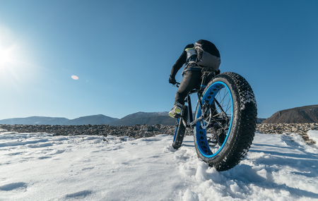 Fatbike (also called fat bike or fat-tire bike) - Cycling on large wheels. Teen rides a bicycle through the snow mountains in the background. Archivio Fotografico