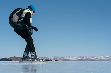 distances: Tourists travel to Norway hiking ice skating on the frozen lake. Special long skate for long distances. Mounting under the ski boots. Location of Lake Baikal action. The Russian called Bayes or Loft. Stock Photo