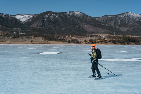 Tourists travel to Norway hiking ice skating on the frozen lake. Special long skate for long distances. Mounting under the ski boots. Location of Lake Baikal action. The Russian called Bayes or Loft. Stock Photo