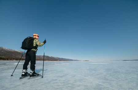 distances: Norwegian hiking skates. Tourists travel to Norway hiking ice skating on the frozen lake. Special long skate for long distances. Mounting under the ski boots. Location of Lake Baikal action. An experimental tour skates for prolonged trips to the ice. Stock Photo
