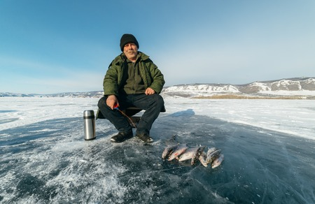 Fisherman is a man in winter fishing. A real fisherman is sitting and fishing. Sometimes pulls ice from the hole to prevent it from freezing. Nearby is a fish caught omul and grayling, another thermos and a hand icebreaker.