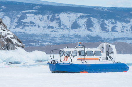 hovercraft: Hovercraft. Ice on the surface of the transparent frozen Lake Baikal. Transport on ice. A lifeboat on an air cushion is parked near a high cliff. Under it is snow and ice. They are rescuers from Russia. Siberia, Lake Baikal. Stock Photo