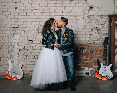 Wedding in the style of rock. Rocker or Biker wedding. Guys with stylish leather jackets. Its a rocknroll baby! Фото со стока - 95155907