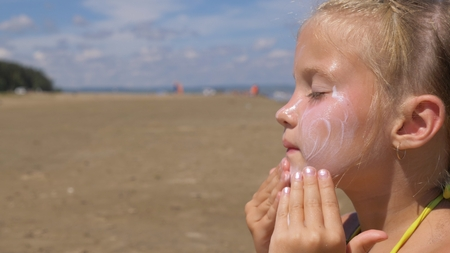 The girl apply sunscreen to face and body. The girl squeezes the sunscreen into her palm and puts it on her face.