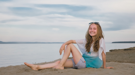One beautiful teenage girl with brown hair outside on a beautiful summer day. The woman is sitting on the beach. The sun was gone in the sunset. The girl is genuinely genuinely genuinely smiling and laughing.