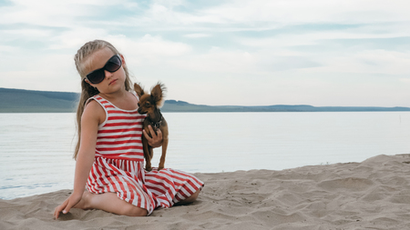 One children sitting on the beach and dog. Kid play with dog. They squeeze them, throw them up. The girl are wearing sunglasses. Dog Toy Terrier.