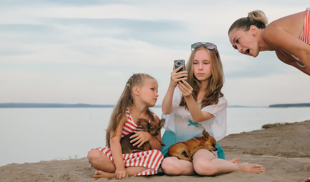 Two teenage are sitting on a sandy beach. Near them is the mother of the girls. The sisters show the parent something on the Internet. Mom is in shock. They have two dogs.