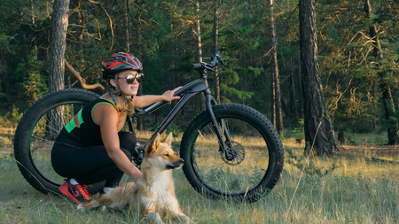 Fat bike also called fatbike or fat-tire bike in summer riding in the forest. Beautiful girl and her bicycle in the forest. She met the dog in the woods and stroked her. The dog is very kind and good.