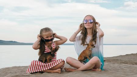 Due adolescenti sono seduti su una spiaggia di sabbia vicino al mare. Ragazza che gioca, parla tra di loro. Hanno due cani. I bambini provano vere emozioni di felicità.