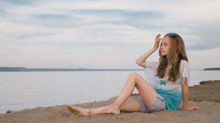 One beautiful teenage girl with brown hair outside on a beautiful summer day. The woman is sitting on the beach. The sun was gone in the sunset.