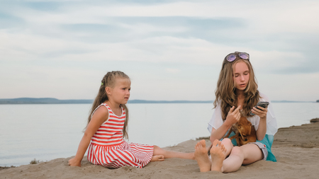 Two teenage are sitting on a sandy beach. They wear sunglasses. Sisters talk to each other and selfie on phone. They have two dogs. Girls correspond, playing, on the Internet.