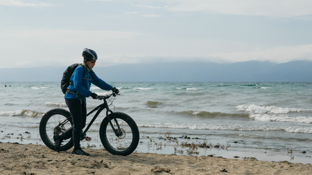 Fat bike also called fatbike or fat-tire bike in summer driving on the beach. Stock Photo